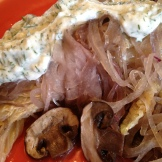 Serving of napa cabbage, red onions, and mushrooms topped with dilled yogurt sauce