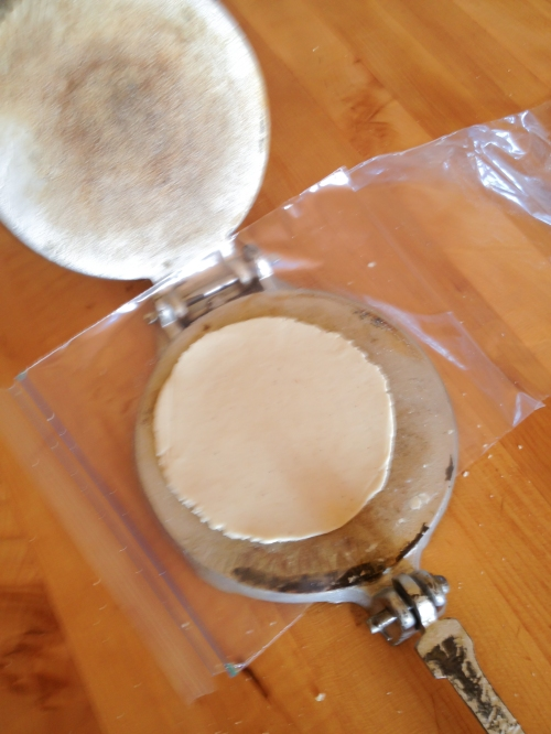 A pressed tortilla ready to be tranferred from the plastic to the palm of the hand and then the hot comal