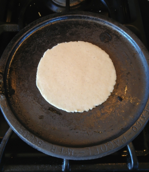 Freshly-pressed tortilla baking on the hot comal