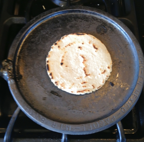 Flipped over to be baked on the second side, this tortilla shows the color and brown spots from a well-heated comal