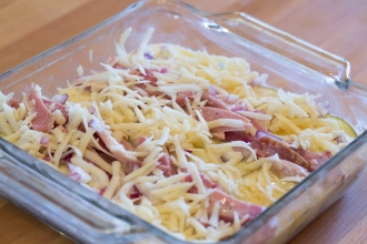 First layer of alternating rows of thin potato slices and ham, topped with onions and Swiss cheese