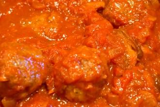 Meatballs simmering in spaghetti sauce