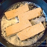 Slices of scrapple frying in butter