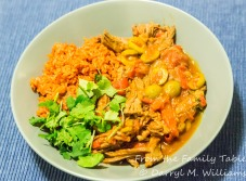 Ropa vieja and yellow rice garnished with cilantro leaves