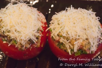 Stuffed tomatoes topped with grated Parmesan cheese and ready for the oven