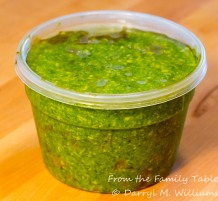 Pesto stored under olive oil in an air-tight container, refrigerated