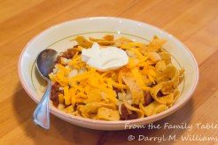 Chili with onion, cheddar cheese, Frito chips and sour cream.