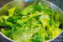 Chopped mustard greens cooking with oil, vinegar, and Louisiana hot sauce