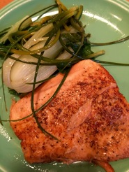 Butter-fried salmon with braised bok choy and garlic scapess