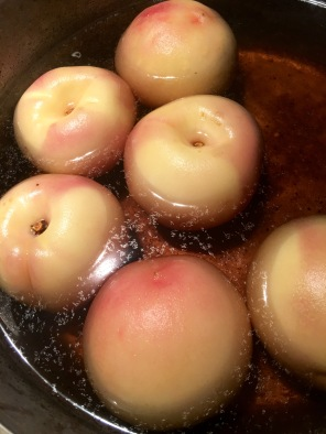 Peaches, skins on, poaching in vanilla-flavored syrup